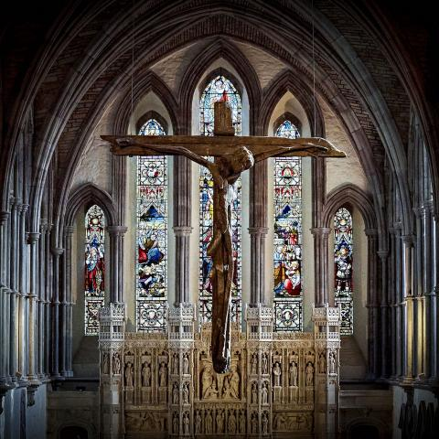 Image of interior of Brecon Cathedral, stain glass window in background with wooden cross in foreground