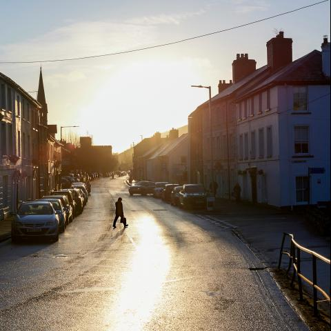 Street in Brecon in the sunshine with the silhouette of a man crossing